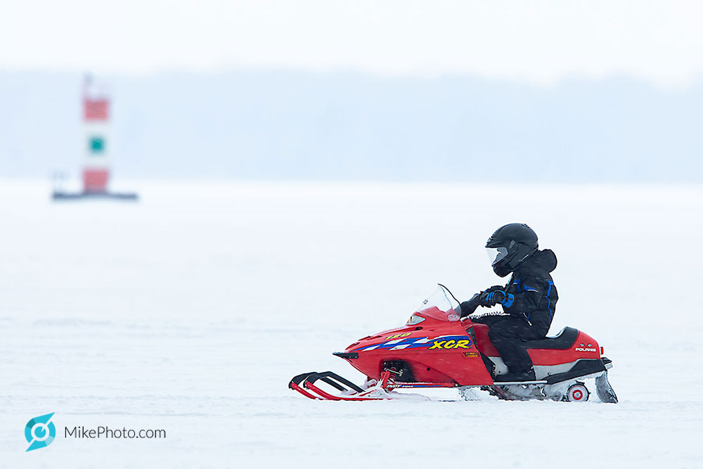 Child on snowmobile passing, in approx. 34 feet water depth with daymark in the background