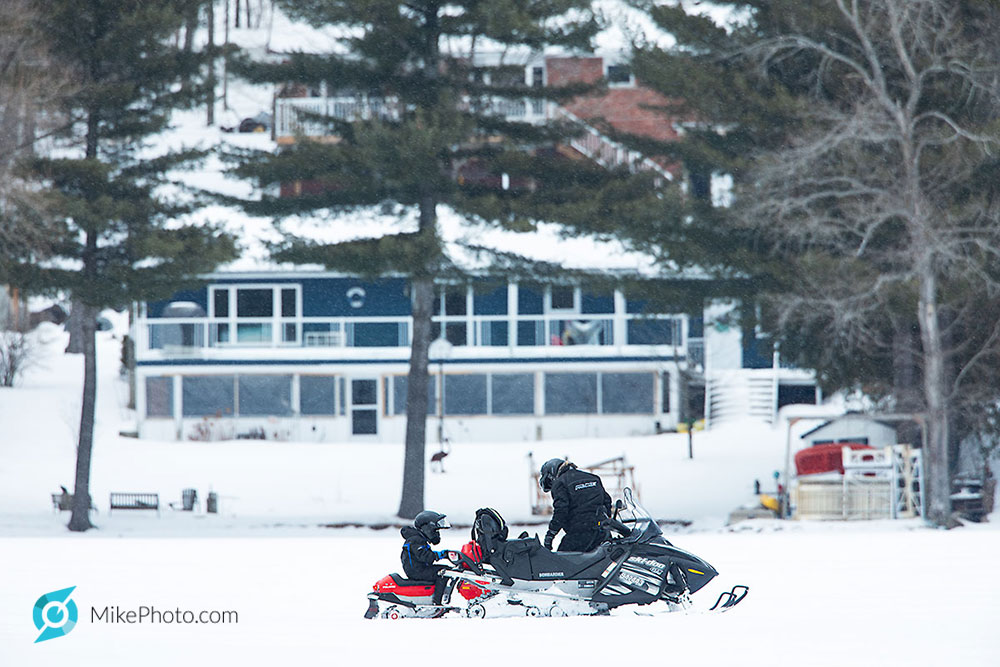 Father and child on snowmobiles