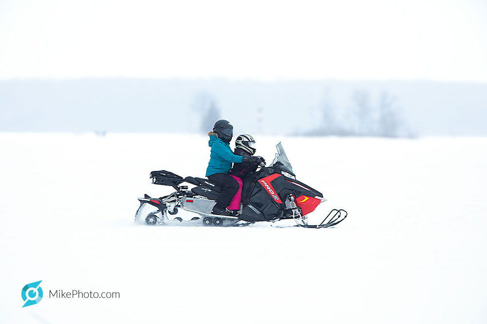 Mom with child, snowmobiling at good speed on Georgian Bay