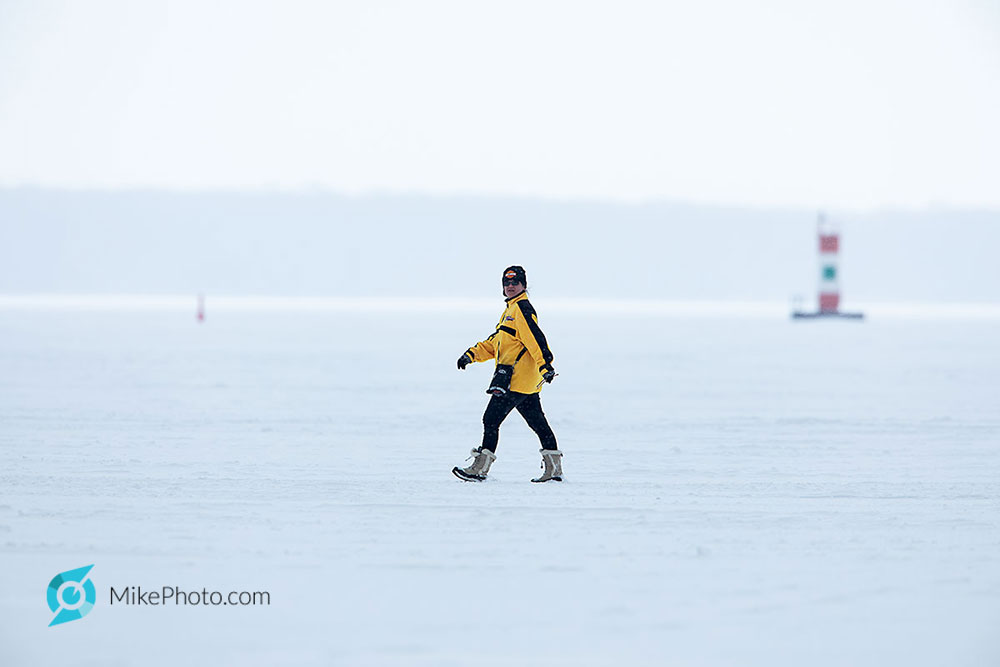 Woman walking on frozen bay with the Penetang Harbour daymark in the background